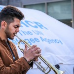 Refugee and asylum-seeking children perform a pop-up philharmonic concert in central Stockholm. Ameer, 15, is a refugee from Syria. He has never played the trumpet before joining the band.